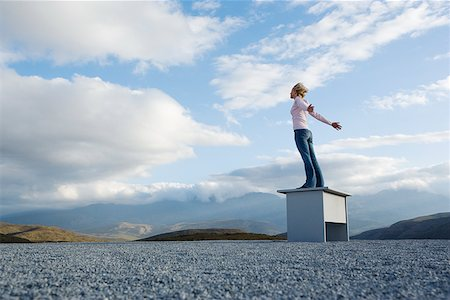 Woman outdoors standing on a desk leaning into the wind Stock Photo - Premium Royalty-Free, Code: 635-01489382