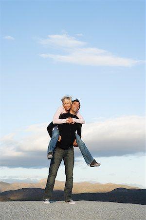 Man giving woman a piggy-back ride Stock Photo - Premium Royalty-Free, Code: 635-01489390