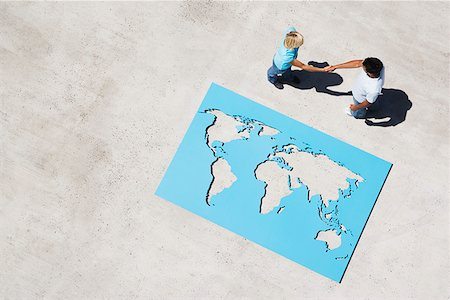 Aerial View of man and woman shaking hands with world map outdoors Stock Photo - Premium Royalty-Free, Code: 635-01489420
