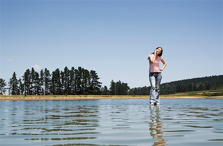 Woman standing on water with cell phone Stock Photo - Premium Royalty-Free, Code: 635-01489560