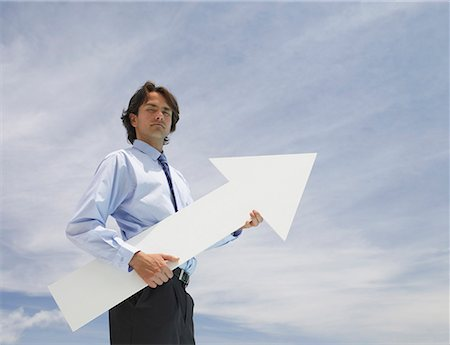 Businessman outdoors holding blank arrow with sky in background Stock Photo - Premium Royalty-Free, Code: 635-01594086