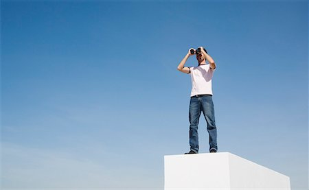 Man on pedestal with binoculars and blue sky outdoors Stock Photo - Premium Royalty-Free, Code: 635-01594231