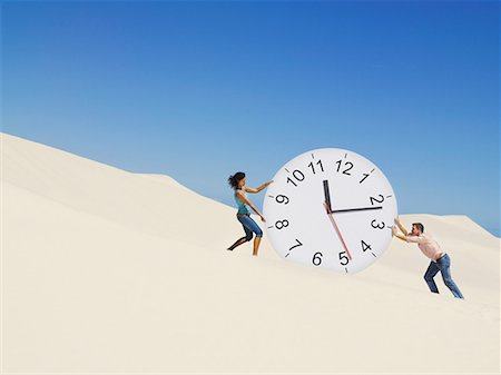 sand clock - A couple pushing a clock in the desert Stock Photo - Premium Royalty-Free, Code: 635-01594497