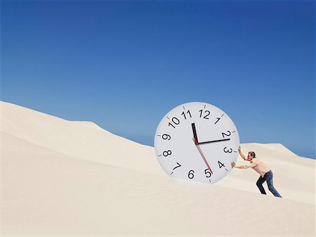 sand clock - A man pushing a clock in the desert Stock Photo - Premium Royalty-Free, Code: 635-01594498