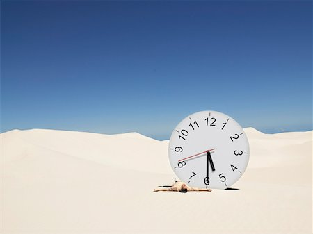 sand clock - A man lying by a clock in the desert Stock Photo - Premium Royalty-Free, Code: 635-01594500