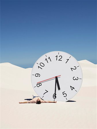 sand clock - A man lying by a clock in the desert Stock Photo - Premium Royalty-Free, Code: 635-01594501