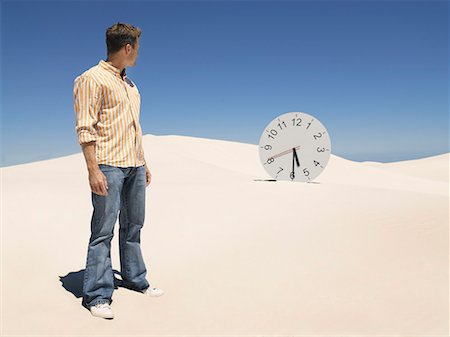 sand clock - A man looking at a clock in the desert Stock Photo - Premium Royalty-Free, Code: 635-01594502