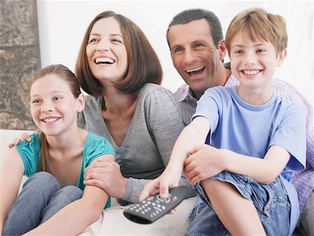 preteen girl boyfriends - Couple with young boy and girl on sofa with television remote Stock Photo - Premium Royalty-Free, Code: 635-01706281