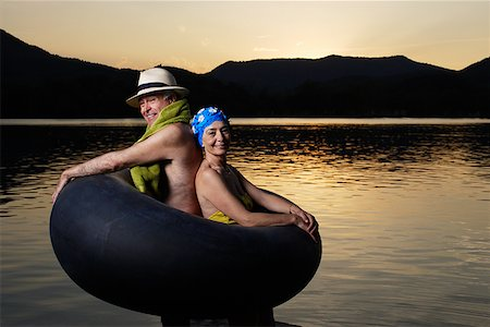 seniors and swim cap - Couple in an inner tube by a lake Stock Photo - Premium Royalty-Free, Code: 635-01707286