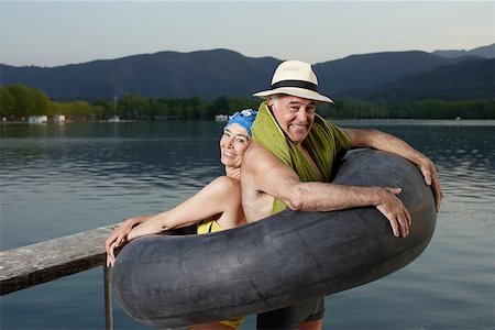 seniors woman in swimsuit - Couple standing in inner tube by lake Stock Photo - Premium Royalty-Free, Code: 635-01707318