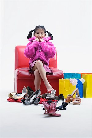 Girl with many shoes around her Stock Photo - Premium Royalty-Free, Code: 635-01707394