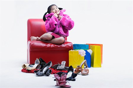 Girl with many shoes around her Stock Photo - Premium Royalty-Free, Code: 635-01707395