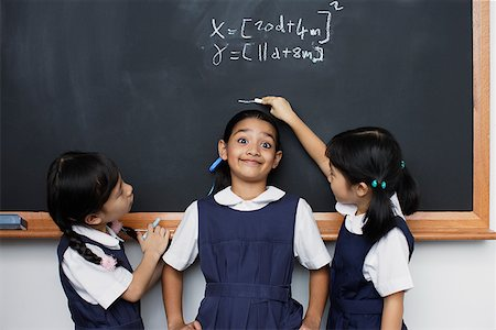 photo of class with misbehaving kids - Two girls marking height of other girl on blackboard Stock Photo - Premium Royalty-Free, Code: 635-01707665