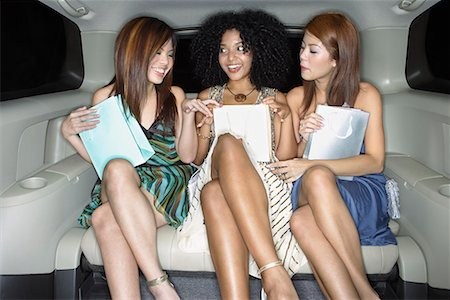 Three women in backseat of limousine with bags Stock Photo - Premium Royalty-Free, Code: 635-01824184