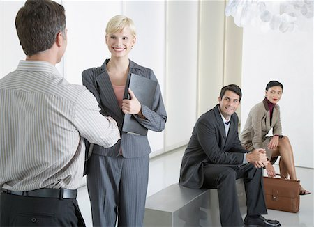 settlement - Two businesspeople shaking hands in office lobby with two businesspeople watching Stock Photo - Premium Royalty-Free, Code: 635-01824607