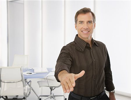 Businessman in boardroom with hand offered for handshake Stock Photo - Premium Royalty-Free, Code: 635-01824627