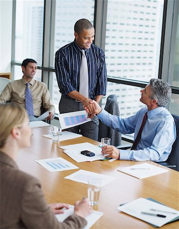 Two businessmen in boardroom shaking hands with two co-workers watching Stock Photo - Premium Royalty-Free, Code: 635-01824724