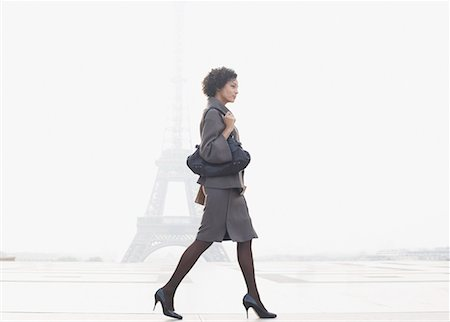 Businesswoman walking in plaza by Eiffel Tower Stock Photo - Premium Royalty-Free, Code: 635-01823540