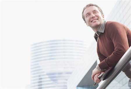 Businessman on balcony holding folders Stock Photo - Premium Royalty-Free, Code: 635-01823622