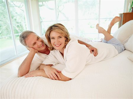 Couple lying in bed being affectionate Stock Photo - Premium Royalty-Free, Code: 635-01823813