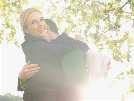 Couple embracing outdoors smiling Stock Photo - Premium Royalty-Free, Code: 635-02051158