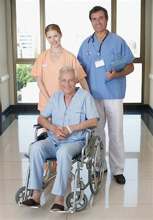 Two hospital workers in corridor with senior patient in wheelchair smiling Stock Photo - Premium Royalty-Free, Code: 635-02051409