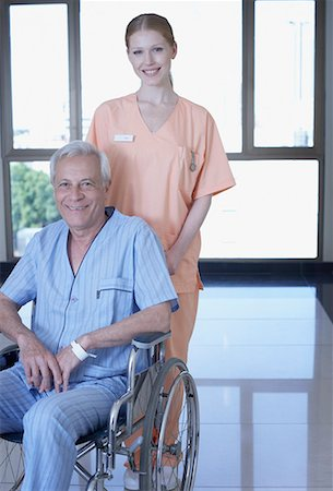 Hospital worker in corridor with senior patient in wheelchair smiling Stock Photo - Premium Royalty-Free, Code: 635-02051410