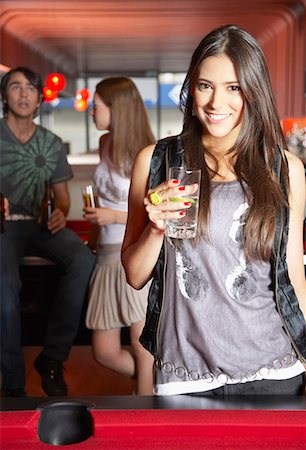 Woman with beverage by pool table smiling Stock Photo - Premium Royalty-Free, Code: 635-02051436