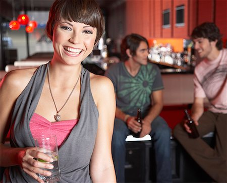 Woman with beverage standing by pool tables smiling Stock Photo - Premium Royalty-Free, Code: 635-02051447