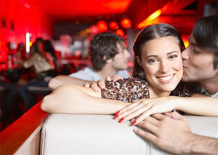 Couple kissing in booth at nightclub and smiling Stock Photo - Premium Royalty-Free, Code: 635-02051440