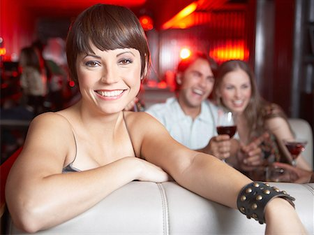 Woman sitting in booth at nightclub smiling Stock Photo - Premium Royalty-Free, Code: 635-02051442