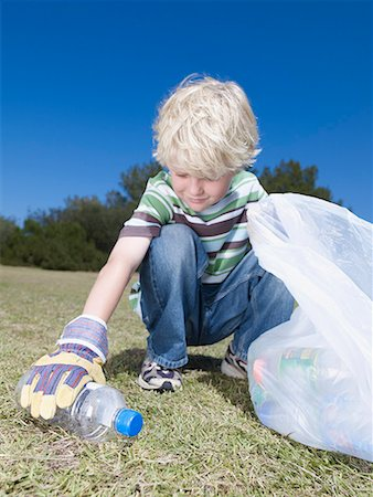 Young boy outdoors picking up empty plastic bottle to put into bag Stock Photo - Premium Royalty-Free, Code: 635-02051583