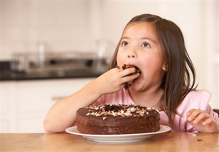 Young girl in kitchen being messy eating cake Stock Photo - Premium Royalty-Free, Code: 635-02051736
