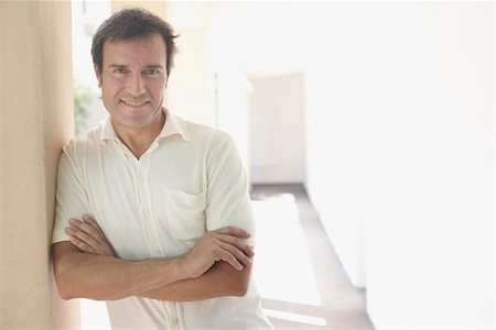 Man outdoors leaning on wall smiling Stock Photo - Premium Royalty-Free, Code: 635-02051880