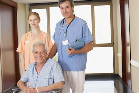 Two hospital workers in corridor with senior patient in wheelchair smiling Stock Photo - Premium Royalty-Free, Code: 635-02052028