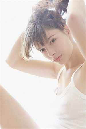 Woman indoors putting hair up Stock Photo - Premium Royalty-Free, Code: 635-02052054