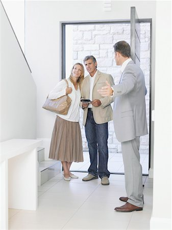 Real estate agent showing couple new home Stock Photo - Premium Royalty-Free, Code: 635-02152199