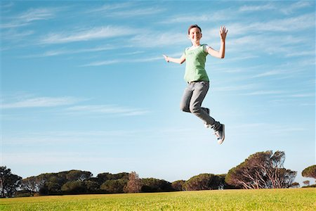Young girl jumping in mid-air in park Stock Photo - Premium Royalty-Free, Code: 635-02152316