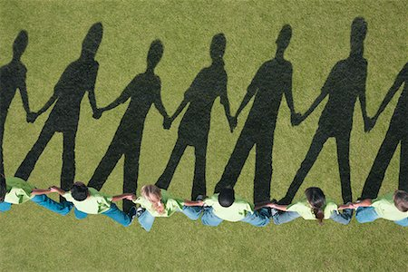 Shadows of children holding hands in a line Stock Photo - Premium Royalty-Free, Code: 635-02152367
