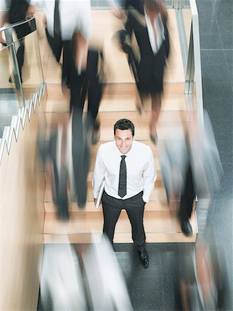 Calm businessman standing in busy office Stock Photo - Premium Royalty-Free, Code: 635-02312491