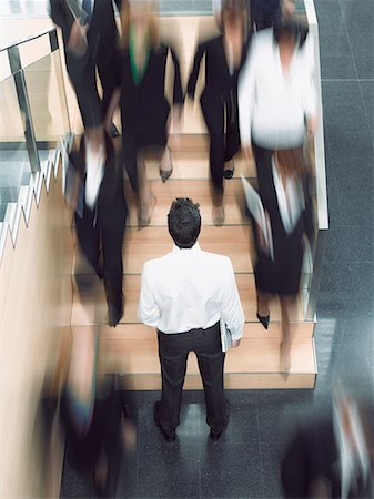 Businessman looking up busy office staircase Stock Photo - Premium Royalty-Free, Code: 635-02312536