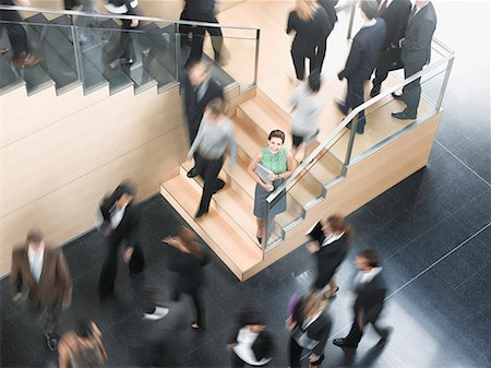 Businessman leaning on busy office staircase Stock Photo - Premium Royalty-Free, Code: 635-02312537