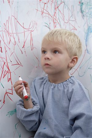 Boy scribbling on whiteboard Stock Photo - Premium Royalty-Free, Code: 635-02312869
