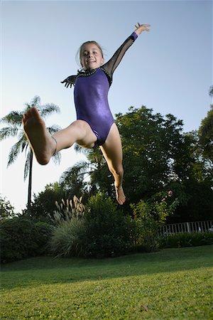 preteen girls stretching - Girl practicing gymnastics in backyard Stock Photo - Premium Royalty-Free, Code: 635-02312888