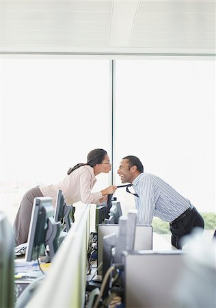 Businesswoman kissing co-worker in office Stock Photo - Premium Royalty-Free, Code: 635-02614456