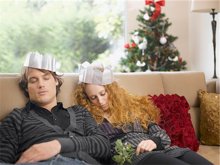 Sleeping couple wearing paper crowns at Christmas Stock Photo - Premium Royalty-Free, Code: 635-02614671