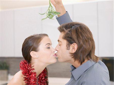 Couple kissing underneath mistletoe Stock Photo - Premium Royalty-Free, Code: 635-02614695