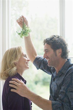 Couple kissing underneath mistletoe Stock Photo - Premium Royalty-Free, Code: 635-02614718