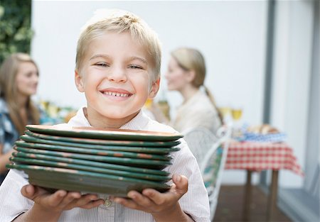 Boy carrying plates to picnic Stock Photo - Premium Royalty-Free, Code: 635-02614848