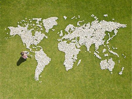 Girl watering world map made of rocks Stock Photo - Premium Royalty-Free, Code: 635-02681717